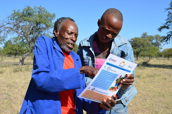 Men discussing Amalima project materials
