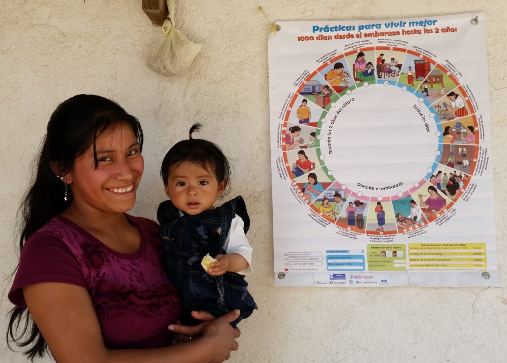 A mother and child stand in front of the Wheel of Practices in Guatemala.