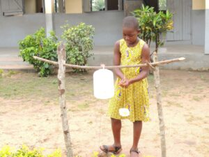 Ghanaian girl washes her hands with soap and clean water.